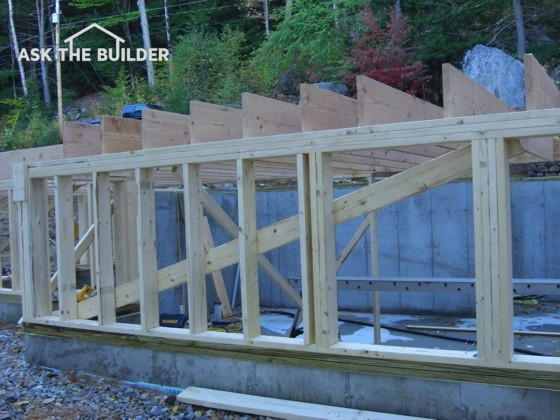These floor joists are resting on an exterior bearing wall, while on the other end they sit in metal joist hangers nailed to a wood beam.  Photo Credit: Tim Carter