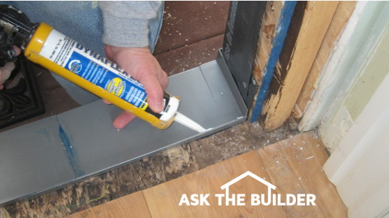 The door flashing is in place and a bead of caulk is being laid down to prevent air infiltration. Photo Credit Tim Carter & Exterior Door Flashing Ninja Tricks - Ask the Builder