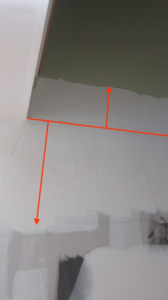 The slanted line runs along the high point of a hump in the wall. The shorter lines with arrow heads show the wide areas of joint compound added to hide the hump. Photo Credit: Tim Carter