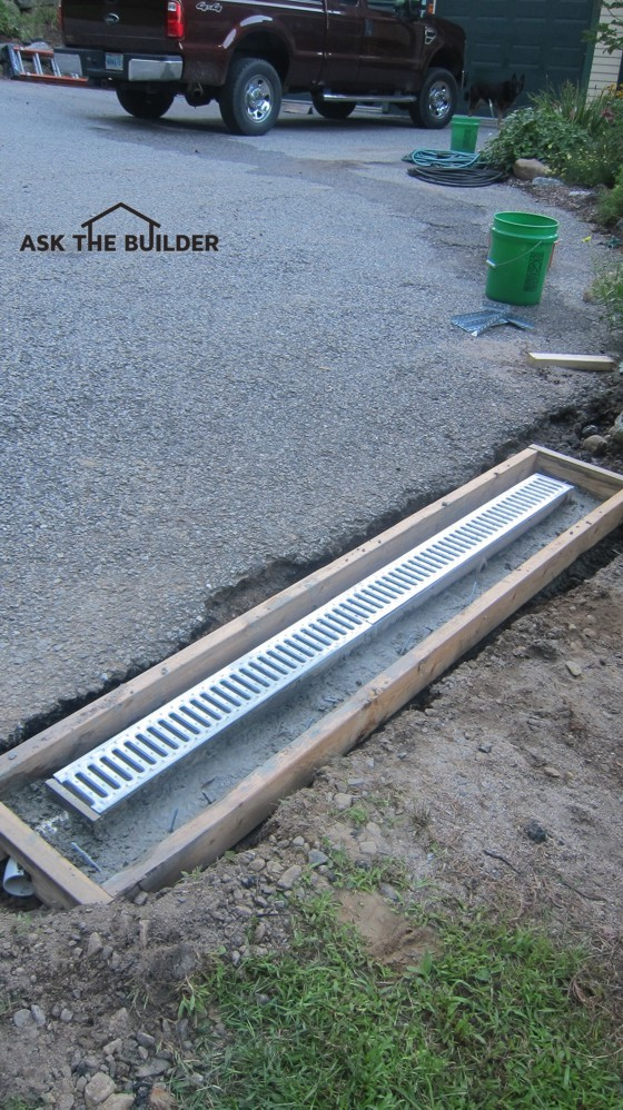 This trench drain will collect water that's rushing off the driveway. More concrete needs to be added between the drain body and the wood form. Photo Credit: Tim Carter