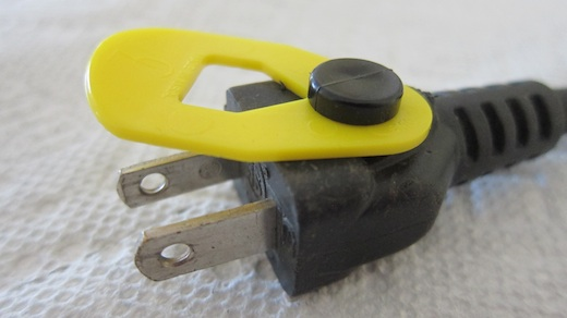 The yellow piece of plastic is the CordLatch. It connects to a bump you find on the end of just about any extension cord. The CordLatch ROTATES out of the way if you want to plug the cord into a standard wall outlet.