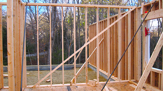 See that angled board nailed to the vertical wall studs? It's a temporary diagonal wall brace used to stabilize the framing while the house is built. © 2016 Tim Carter Builder