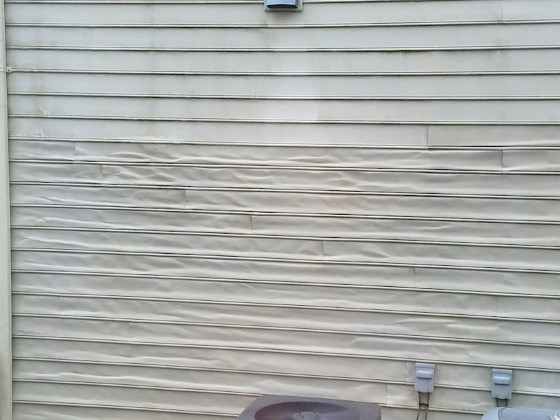 Warped vinyl siding