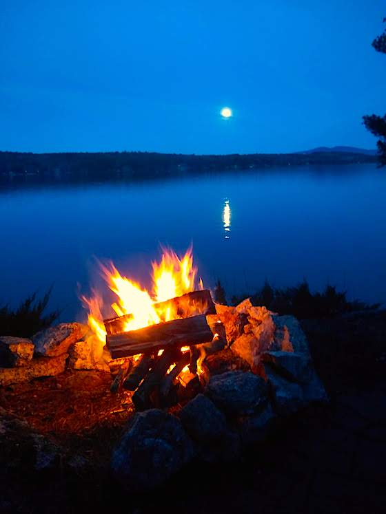 campfire by lake with full moon